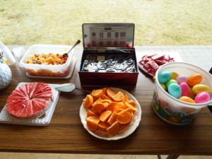 フルーツポンチ、洋菓子の詰め合わせ、キットカット、ラズベリーケーキ、オレンジ、カラフルなイースターエッグ(中身はチョコ菓子)