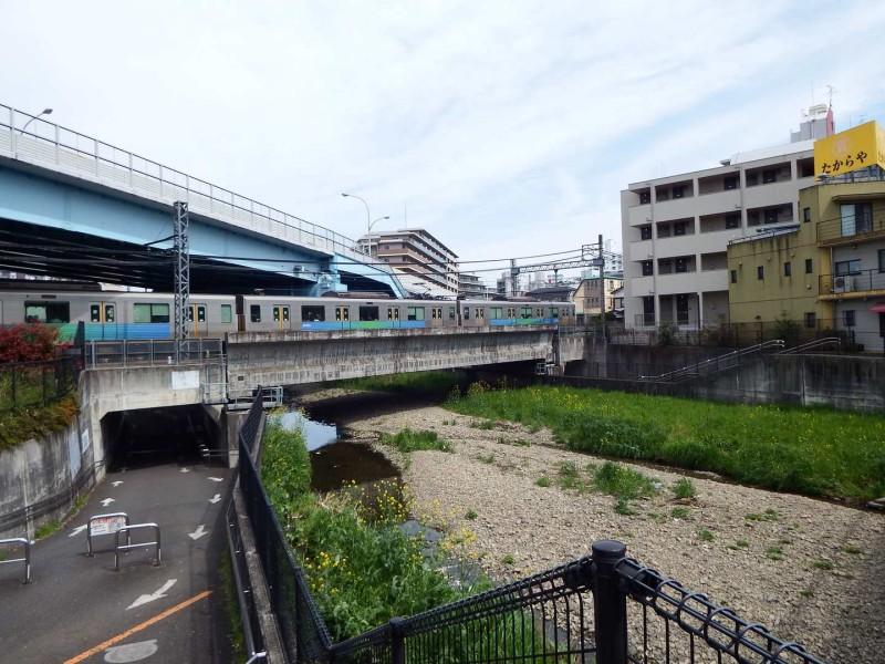 久米川橋の前に西武新宿線の電車が通り、すぐ近くには久米川駅があります。
