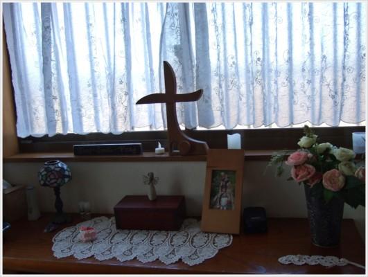 玄関の窓側には素敵な木製の十字架、その下にはファミリーの写真などが飾ってあります。