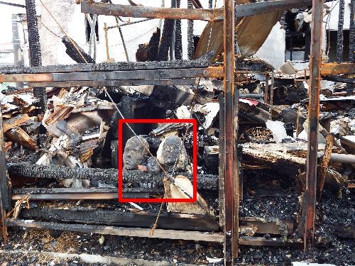 全焼した家の前に焼け焦げた3人の顔の石像